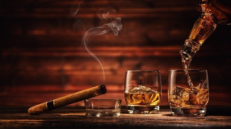 cigar and glasses of whisky on ice