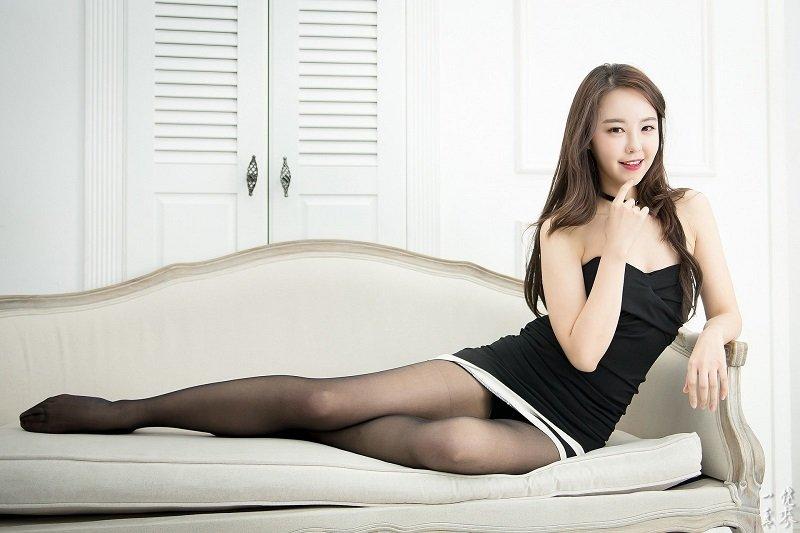 Hot white skin Thai girl wearing a black dress and sitting on a sofa