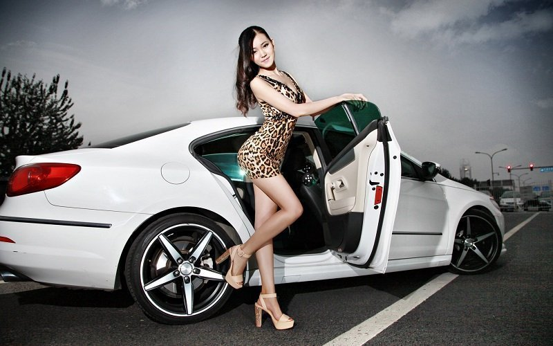Hot Thai girl wearing a leopard dress next to a white limousine