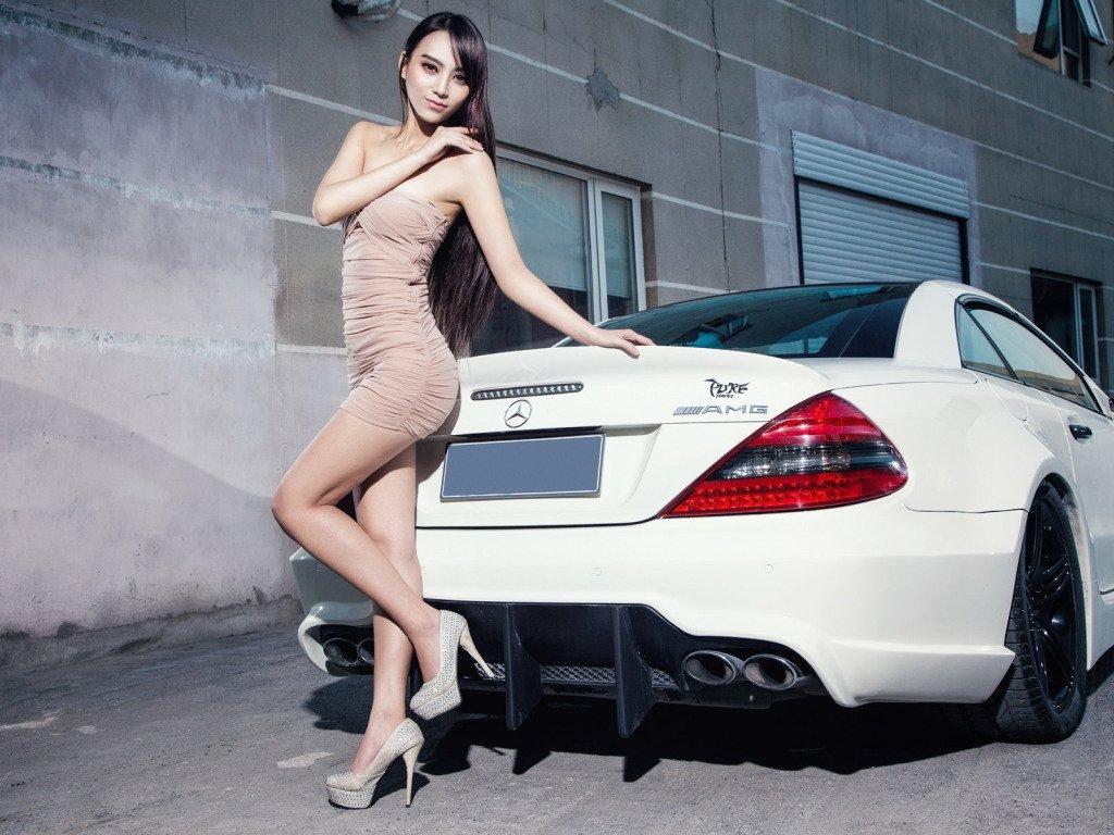 Sexy Thai girl wearing a dress next to an AMG Mercedes car