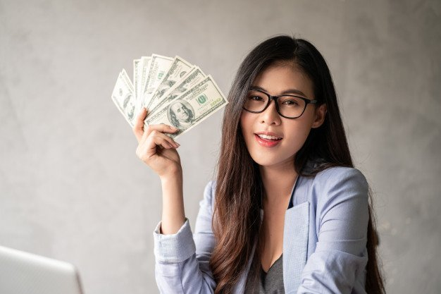 Thai girl with glasses holding dollar bills in her hand