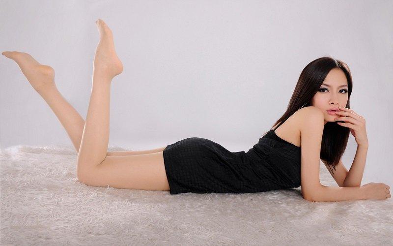 Sexy Thai girl in black dress laying down on fur