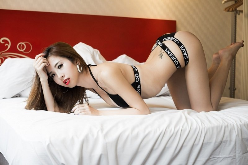 Exciting Thai girl in black lingerie on her knees on a bed