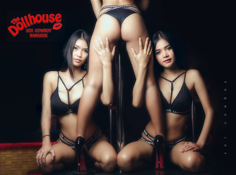 three bar girls from Dollhouse Bangkok gogo bar in Soi Cowboy grabbing the leg of one of the girl